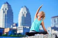 舒展她的肌肉的嬉戏妇女在瑜伽实践前 免版税库存照片