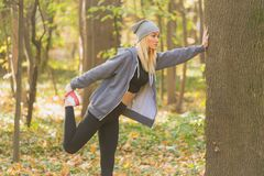 舒展她的肌肉的年轻和适合的妇女 健康和体育概念 免版税库存照片
