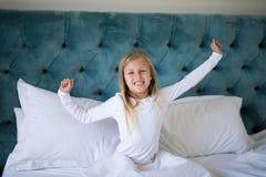舒展她的胳膊的女孩,当醒在卧室时 免版税库存照片