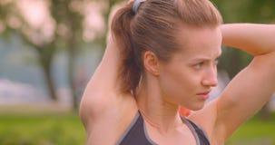 舒展她的胳膊的年轻俏丽的运动的健身女孩特写镜头画象在公园在都市城市户外 股票录像