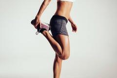 舒展她的腿的健身妇女 免版税库存图片
