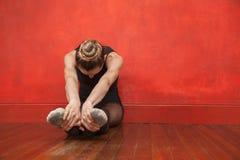 舒展她的腿的跳芭蕾舞者在舞蹈演播室 免版税图库摄影