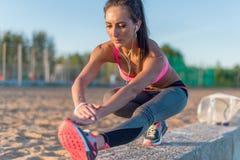 舒展她的腿筋,腿的健身式样运动员女孩准备和  行使与耳机的少妇 免版税库存图片