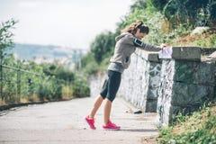 舒展对岩石墙壁的妇女赛跑者 库存照片