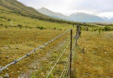 舒展往雪加盖的山的铁丝网篱芭 免版税库存照片