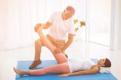 舒展怀孕的夫人腿的生理治疗师 免版税库存照片