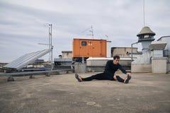 舒展户外在屋顶的一个年轻人 免版税库存照片