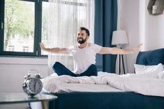 舒展的睡衣的年轻人,当坐床在早晨时 免版税库存照片