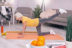 舒展的运动年长妇女在瑜伽席子 免版税库存图片