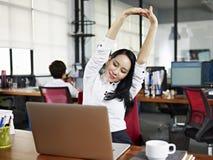 舒展胳膊的亚裔女商人在办公室 免版税图库摄影