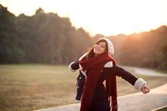 舒展胳膊的女孩放松与日落 库存图片