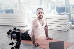 舒展腹部肌肉的被启发的男性博客作者 免版税库存图片