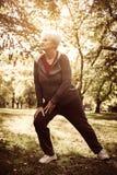 舒展腿和锻炼的活跃资深妇女在公园 免版税库存图片