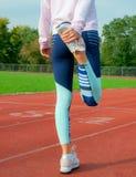 舒展腿的健身妇女在户外的奔跑前 免版税图库摄影