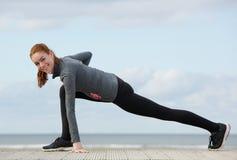 舒展腿的微笑的运动的妇女 免版税图库摄影