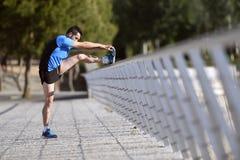 舒展腿的运动员人给小牛加热在倾斜在栏杆城市都市公园的连续锻炼前干涉 免版税库存图片