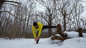 舒展腿的运动的亭亭玉立的人在跑前在冬天森林里 影视素材