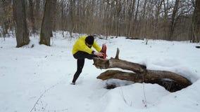 舒展腿的黄色外套的有胡子的体育人在冬天森林里在降雪 股票录像
