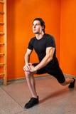 舒展腿的黑sportwear的年轻运动员在健身房锻炼前对明亮的橙色墙壁 免版税图库摄影
