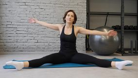 舒展臀部,腿筋肌肉,腿肌肉的瑜伽席子年轻运动妇女户内在健身房 r 影视素材