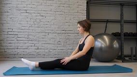 舒展臀部,腿筋肌肉,腿肌肉的瑜伽席子年轻运动妇女户内在健身房 r 股票视频