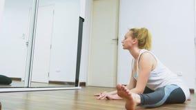 舒展靠近镜子的妇女在她的公寓 一种健康生活方式,不是一个职业体育的概念 影视素材