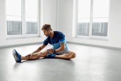 舒展锻炼 舒展在锻炼前的英俊的健康人 免版税库存照片