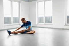 舒展锻炼 舒展在锻炼前的英俊的健康人 库存照片