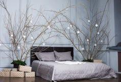 舒适、舒适、内部和假日概念-有床和圣诞节诗歌选的舒适卧室在家点燃 免版税库存图片