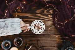 舒适与圣诞灯、妇女手用素食主义者可可粉,玻璃、被编织的毛线衣和蜡烛的冬天flatlay安排在黑暗 库存照片
