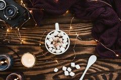 舒适与圣诞灯、素食主义者可可粉、玻璃、被编织的毛线衣和蜡烛的冬天flatlay安排 免版税库存图片