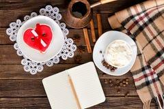 舒适休息热奶咖啡,心形的蛋糕,有铅笔的一个笔记本,罐咖啡 顶视图 免版税库存图片