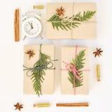 舒适假日白色背景 圣诞节结构的云杉的分支、礼物、闹钟、桂香、茴香和五彩纸屑在小 库存图片