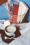 舒适冬天周末在家 早晨用咖啡或可可粉,书,温暖被编织的一揽子和北欧样式椅子 Hygge概念 库存图片