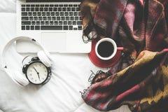 舒适冬天家庭背景,杯子热的咖啡用蛋白软糖,温暖在白色床背景的被编织的毛线衣, 库存照片