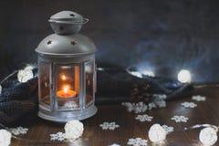 舒适冬天家 灯笼,一个蜡烛,诗歌选,雪花 免版税图库摄影