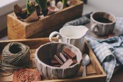 舒适冬天早晨在家 咖啡、牛奶和巧克力在木盘子 在背景的风信花花 温暖的心情 免版税库存图片