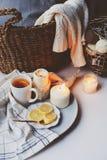 舒适冬天早晨在家 热的茶用柠檬、被编织的毛线衣和现代金属内部细节 免版税库存照片