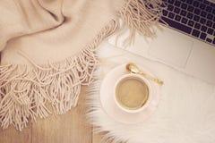 舒适冬天早晨 咖啡、膝上型计算机和一条温暖的围巾在一张白色毛皮地毯在地板上 免版税库存照片