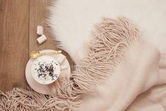 舒适冬天早晨 热奶咖啡和一条温暖的围巾在一张白色毛皮地毯在地板上 库存图片