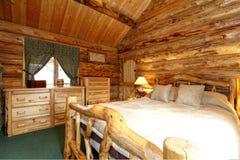 舒适卧室在原木小屋房子里 免版税库存图片