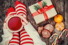 舒适圣诞节在家 妇女在圣诞节长袜、大礼物、茶,糖果和曲奇饼巧克力的` s脚在bokeh点燃b 免版税库存图片