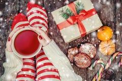 舒适圣诞节在家 拿着一杯茶,妇女在圣诞节长袜,大礼物的` s脚的女性手 免版税图库摄影