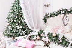 舒适圣诞节家内部 在结构树的重点 装饰新年度 有大双人床的明亮的卧室室 免版税图库摄影
