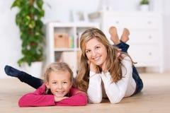 舒适地说谎在地板上的母亲和女儿 免版税库存图片