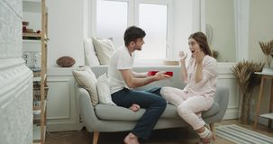 舒适大气公寓,庆祝华伦泰s天,人的夫妇给他的女朋友一个当前红色箱子,他们是 股票视频