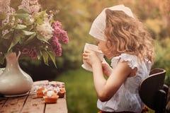 舒适室外茶会的逗人喜爱的儿童女孩在有丁香花束的春天庭院里  库存照片