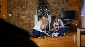 舒适家庭房子 坐地板和读书的年轻幸福家庭对婴孩 股票录像