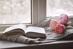 舒适家庭静物画:春天花和被打开的书与温暖的格子花呢披肩在窗台 春天概念,赠送阅本空间 图库摄影