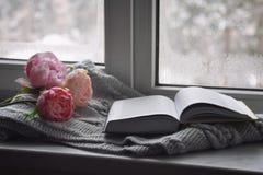 舒适家庭静物画:杯子热的咖啡、春天花和被打开的书与温暖的格子花呢披肩在窗台反对雪 免版税库存照片